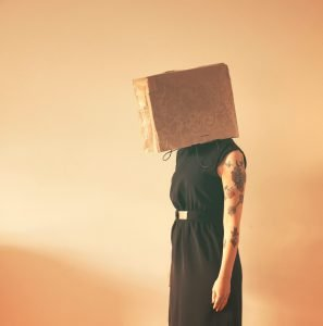 Woman with box over head. Photo by Deborah Bacheschi, via Unsplash